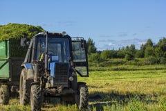 Is een tractor met een lichaam met groen gras tegen een achtergrond van groene weide en blauwe hemel wordt gevuld die Royalty-vrije Stock Foto