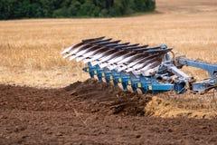 Een tractor met een ploeg behandelt de grond royalty-vrije stock afbeeldingen