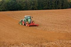 Een tractor ploegende grond Stock Foto