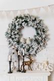 Een traditionele heldere Kerstmiskroon die over de open haard hangen, op een witte bakstenen muur, huisdecor voor de wintervakant royalty-vrije stock afbeeldingen