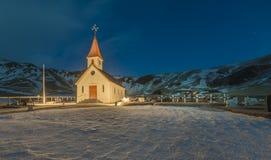 Een traditionele Ijslandse kerktribunes trots bij de voet van een kleine berg, in zuidelijk IJsland royalty-vrije stock afbeelding