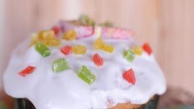 Een traditionele Pasen-cake die met marmelade en gekonfijte vruchten wordt verglaasd en wordt verfraaid roteert met gekleurde bin stock videobeelden