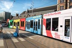 Een tram bij de Centrale post van Amsterdam en een vrouwen dragende zakken wordt tegengehouden kruist de spoorweg die royalty-vrije stock fotografie