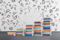 Een trede wordt gemaakt van kleurrijke boeken De onderwijspictogrammen worden getrokken op de concrete muur Royalty-vrije Stock Fotografie