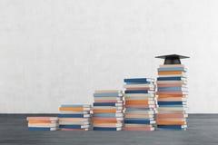 Een trede wordt gemaakt van kleurrijke boeken Een graduatiehoed is op de definitieve stap Stock Afbeelding