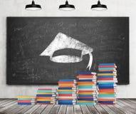 Een trede wordt gemaakt van kleurrijke boeken Een graduatiehoed wordt getrokken op het zwarte bord Concrete muur, houten vloer en Stock Afbeelding