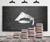 Een trede wordt gemaakt van kleurrijke boeken Een graduatiehoed wordt getrokken op het zwarte bord Concrete muur, houten vloer en Royalty-vrije Stock Afbeeldingen
