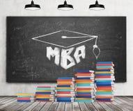 Een trede wordt gemaakt van kleurrijke boeken Een graduatiehoed wordt getrokken op het zwarte bord Mbaconcept Concrete muur, hout Stock Afbeeldingen