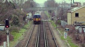 Een trein gaat een spoorwegovergang in Londen over stock video