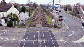 Een trein gaat een spoorwegovergang in Londen over stock videobeelden
