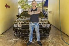 Een trotse jonge mens bevindt zich voor zijn zeepachtige auto royalty-vrije stock foto's