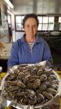 Een trotse oesterlandbouwer pronkt met haar productie in Cap Ferret, Frankrijk stock fotografie