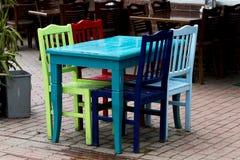 Een turkooise lijst, en groene, rode, blauwe en donkerblauwe stoelen van een restaurant op sideway royalty-vrije stock afbeelding