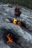 Een Turkse mens verwarmt zijn hand naast de vlammende die rotsen van Chimère dichtbij Cirali op de Mediterrane kust van Turkije w Stock Foto's
