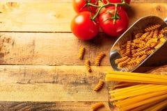 Een twijg van tomaten, Italiaanse spaggeti en deegwaren Op een houten achtergrond Culinaire achtergrond Dieet smakelijk en gezond royalty-vrije stock foto