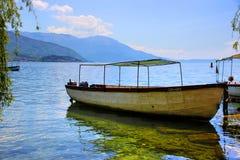 Een twin-engine houten boot met een dak op een cristal duidelijk meer royalty-vrije stock foto's
