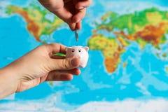 Een uiterst klein spaarvarken wordt gehouden in de hand Een kleurrijke kaart van wor Stock Fotografie