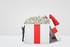 Een uiterst kleine zakenman die in een reusachtig wit en rood hoogtepunt van de giftdoos van geld proberen te krijgen royalty-vrije illustratie