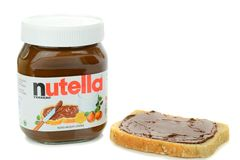 Een uitgespreide kruik Nutella-chocolade en brood Stock Afbeelding