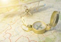 Een uitstekend kompas op de kaart en een vliegtuig stock afbeelding