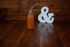 Een uitstekende fles vers gedrukt sap op een houten achtergrond en het gloeien ampersand stock afbeeldingen