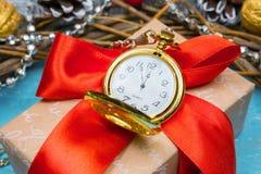 Een uitstekende klok in de sneeuw tegen een achtergrond van een gift en een Kerstmiskroon Royalty-vrije Stock Afbeelding