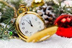 Een uitstekende klok in de sneeuw tegen de achtergrond van een Kerstboom en een slinger Stock Foto