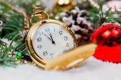 Een uitstekende klok in de sneeuw tegen de achtergrond van een Kerstboom en een slinger Royalty-vrije Stock Afbeeldingen