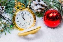 Een uitstekende klok in de sneeuw tegen de achtergrond van een Kerstboom en een slinger Stock Foto's