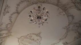 Een Uitstekende Kroonluchter op wit plafond in oud kasteel stock videobeelden