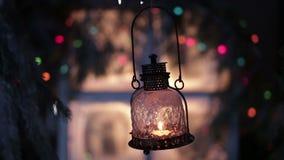 Een uitstekende lantaarn met een kaars op een achtergrond van Kerstmislichten stock videobeelden