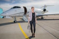 Een uitvoerende bedrijfsvrouw die een vliegtuig verlaten stock afbeeldingen