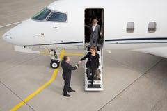 Een uitvoerende bedrijfsvrouw die een vliegtuig verlaten royalty-vrije stock fotografie