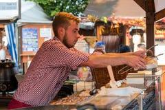 Een undefinite mannelijke persoon op de worstmarkt die en vers gekookt voedsel werken dienen Stock Afbeeldingen