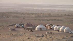 Een Uzbekistani-landschap met hutten en kamelen stock videobeelden