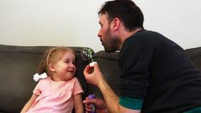 Een vader blaast een zeepbelrecht op zijn dochter` s neus in langzame motie De babylach stock videobeelden