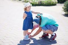 Een vader die zijn kleine dochter met haar schoenen helpen royalty-vrije stock foto's