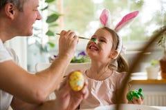 Een vader en een dochter die Pasen vieren, schilderend eieren met borstel stock afbeelding