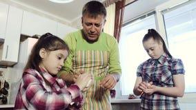 Een vader en twee dochters, ??n die van hen met Benedensyndroom, deeg samen in de keuken maken stock videobeelden