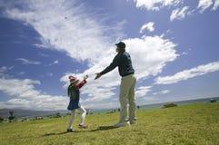 Een vader en zijn jonge dochter die een vlieger vliegen Royalty-vrije Stock Afbeeldingen