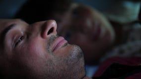 Een vader en een zoon in pyjama's in bed vóór bed gebruiken een gadget stock videobeelden