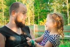 Een vader met een baard houdt een dochter in zijn wapens royalty-vrije stock foto's