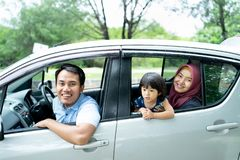 Een vader, een moeder, en een dochter die uit van de open vensters kijken stock afbeelding