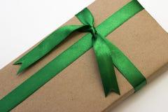 Een vakantiegift in document wordt en met groen lint wordt gebonden verpakt die dat Stock Afbeelding