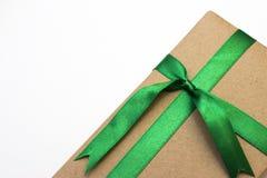 Een vakantiegift in document wordt en met groen lint wordt gebonden verpakt die dat Stock Fotografie
