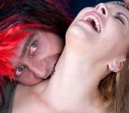 een vampier die jonge mooie vrouw bijt Stock Foto's
