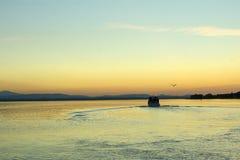 Een veerboot vertrekt van het dok in de vreedzame wateren van het meer bij zonsondergang stock foto