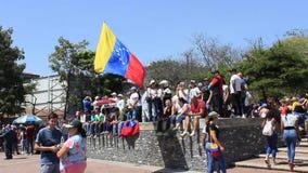 Een Venezolaan houdt vlag als opposities maart tijdens een protest tegen Maduro-overheid in steun tegen Juan Guaido in Caracas stock video