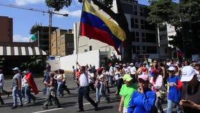 Een Venezolaan houdt vlag als opposities maart tijdens een protest tegen Maduro-overheid in steun tegen Juan Guaido in Caracas stock footage