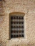 Een venster met decoratieve bars in een bakstenen muur royalty-vrije stock afbeelding
